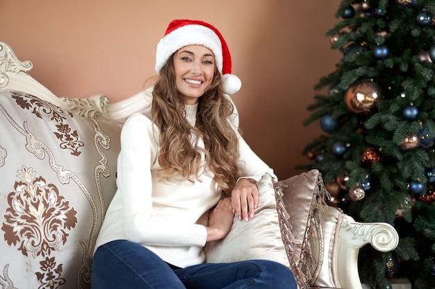 Donna vestita maglione bianco e jeans che si siedono sul pavimento vicino all'albero di natale con la scatola attuale