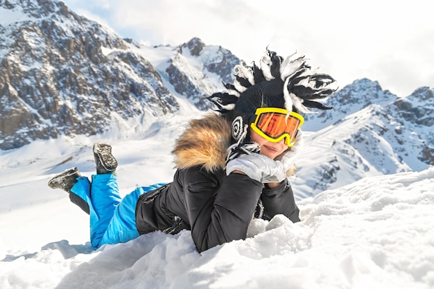 Donna vestita con abiti invernali ritratto occhiali e cappello invernale sdraiato sulla neve in cima alla montagna
