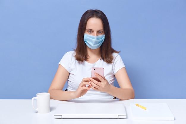 La donna veste la maglietta casuale bianca e il telefono della tenuta della maschera protettiva in mani