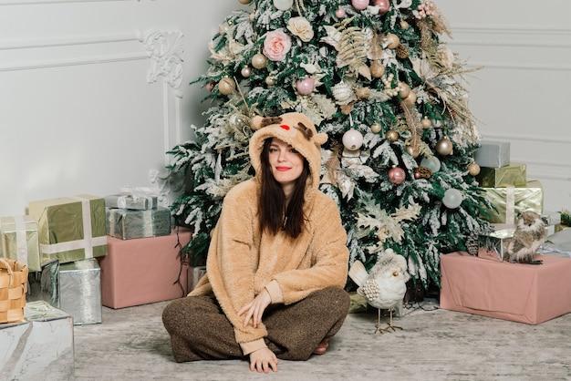 Donna che veste l'albero di natale, sorridente, seduta nell'interno del nuovo anno