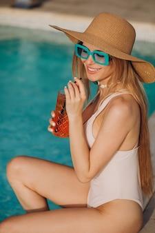 Donna che beve cocktail alcolici a bordo piscina