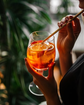 Donna che beve aperol spritz cocktail con una cannuccia da un bicchiere