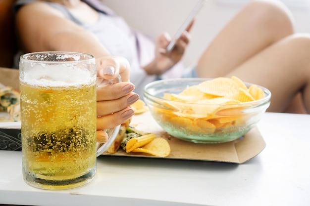 Donna che beve birra a letto con patatine e pizza da vicino
