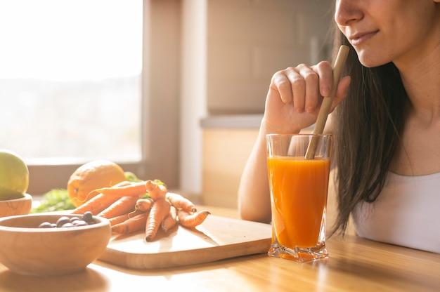 Donna che beve il succo di carota in cucina