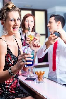 Donna che beve cocktail in un night club di fantasia