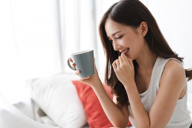 Caffè bevente della donna in camera da letto di mattina
