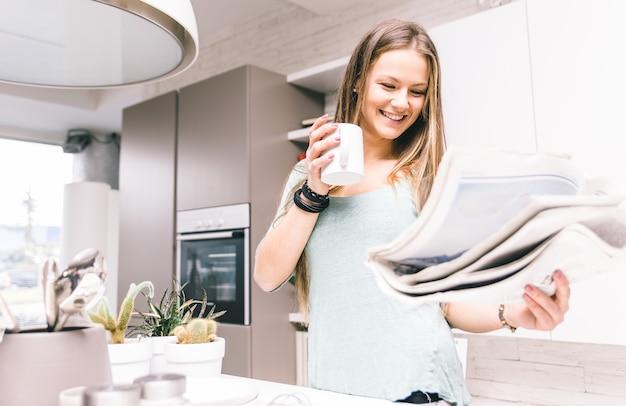 Donna che beve il caffè per la colazione in cucina