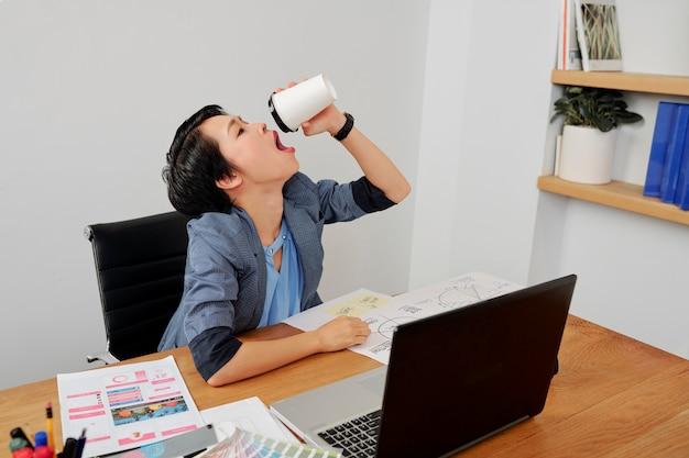 Donna che beve il caffè in ufficio