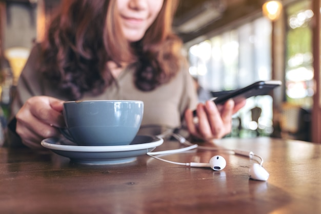 Donna che beve caffè mentre si utilizza il telefono cellulare per ascoltare musica con auricolare sul tavolo di legno nella caffetteria