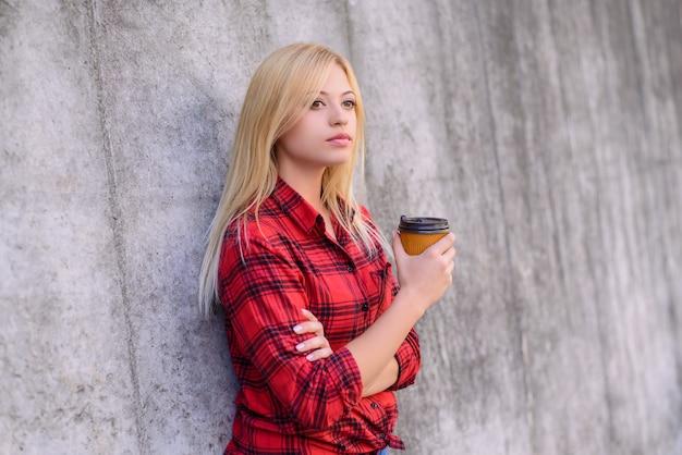 Donna che beve caffè. donna che aspetta la sua amica, in piedi su uno sfondo grigio con le braccia incrociate e con in mano una tazza di caffè