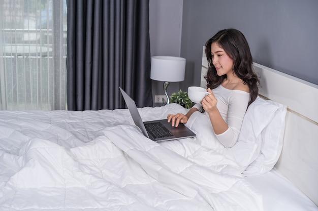 Donna che beve una tazza di caffè e che per mezzo del computer portatile sul letto