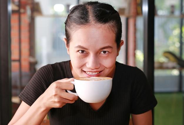 Donna che beve caffè caldo al mattino, con motivo a forma di cuore sulla tazza di caffè.