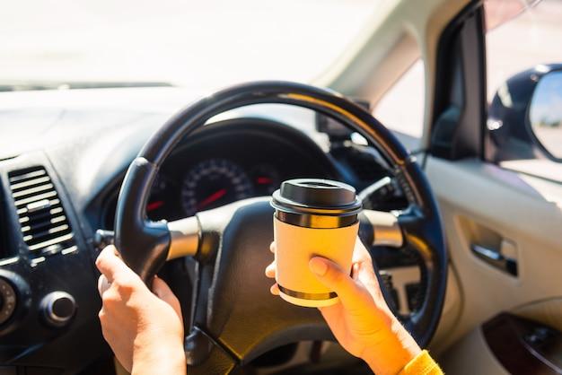 Donna che beve tazza di caffè caldo da asporto all'interno di un'auto e durante la guida dell'auto