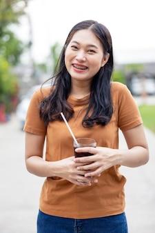 Donna che beve cola di ghiaccio nel bicchiere. bicchiere di cola, bevande analcoliche con ghiaccio., concetto di cibo e bevande.