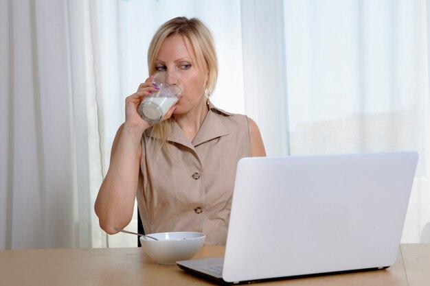 Donna che beve latte da un bicchiere, fa colazione e naviga in internet.
