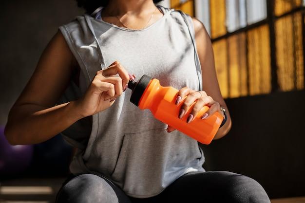 Donna che beve acqua dopo l'allenamento