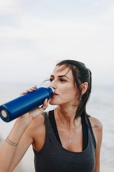 Donna che beve acqua dopo un allenamento