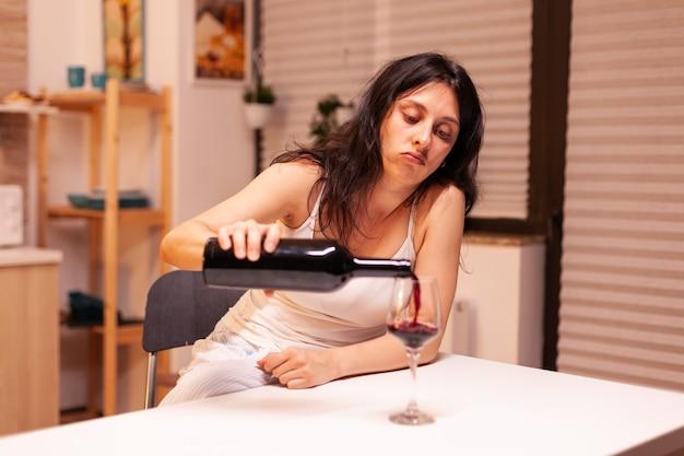 Donna che beve vino da sola durante una crisi di vita. malattia della persona infelice e ansia che si sente esausta per avere problemi di alcolismo.