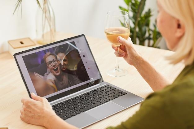 Donna che beve vino e parla con i suoi amici online sul monitor del computer che celebrano un evento