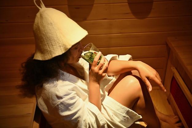 Una donna beve una bevanda salutare mentre fuma in una sauna. terapia di bellezza nella spa. cure sanitarie e trattamenti di bellezza nel centro termale