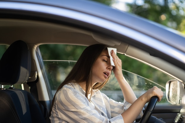 La donna che guida è calda durante l'ondata di caldo in auto che soffre di caldo asciuga il sudore dalla fronte