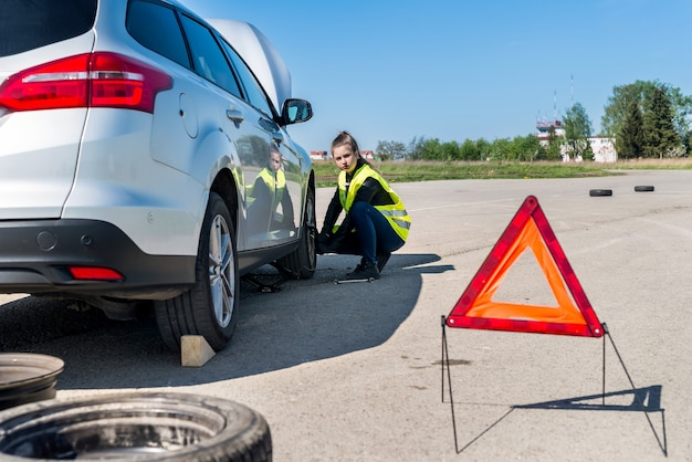 Driver della donna che cambia ruota danneggiata sul ciglio della strada