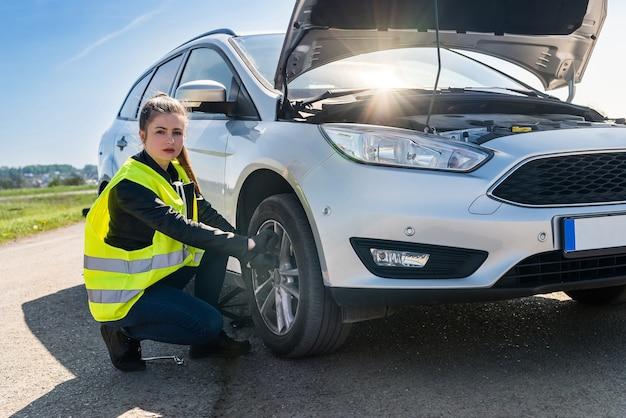 Autista donna sta per cambiare la ruota danneggiata