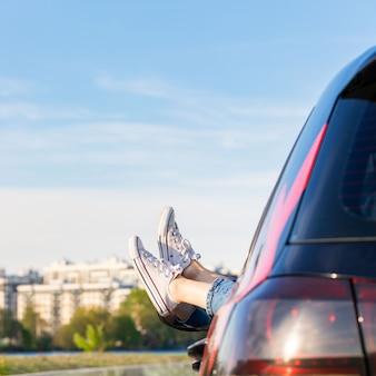 L'autista donna mette i piedi sulla portiera della macchina, rilassarsi, riposare, godersi il momento, sentire l'aria e la libertà