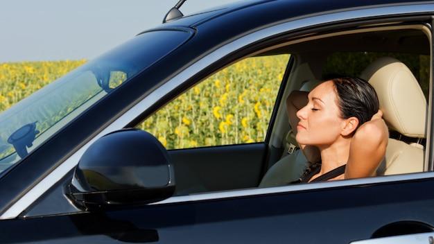 Autista donna che riposa dietro il volante con le mani alzate dietro la testa mentre si prende una pausa per rinfrescarsi durante un lungo viaggio