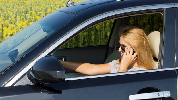 Autista della donna che parla sul suo telefono cellulare con la sua auto accostata in modo sicuro al lato della strada vicino a un campo di girasoli