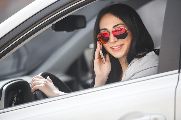 Autista donna parlando al telefono. bella ragazza in macchina. signora alla guida di un'auto bianca.