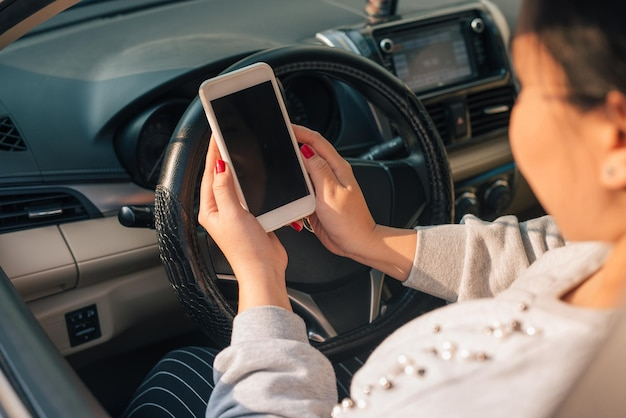 Autista donna che utilizza smartphone in auto durante l'ingorgo stradale, schermo vuoto a scopo di progettazione.