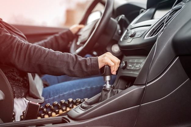 Donna alla guida di auto, mani sul primo piano del volante