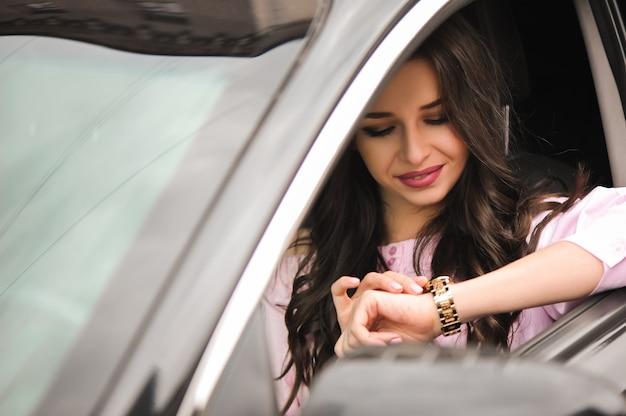 Donna alla guida di un'auto e guardando l'orologio