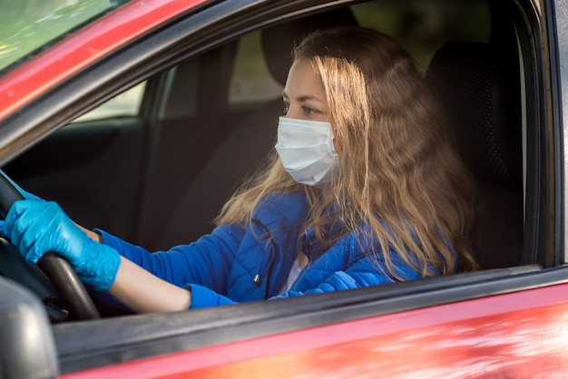 Una donna alla guida di un'auto in maschera protettiva medica e guanti. stile di vita e guida sicura durante un coronavirus pandemico in quarantena