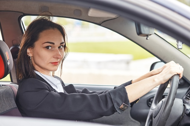 La donna alla guida di un'auto e sorride felicemente con felice espressione positiva durante il viaggio di viaggio, le persone si divertono a ridere il trasporto e la donna felice rilassata sul concetto di vacanza di viaggio su strada