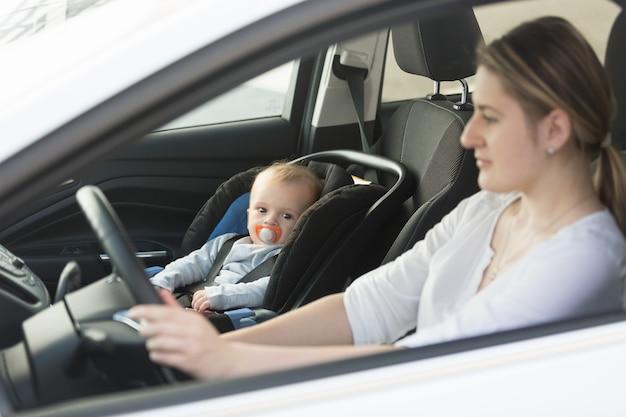 Donna alla guida di un'auto con bambino seduto sul sedile anteriore