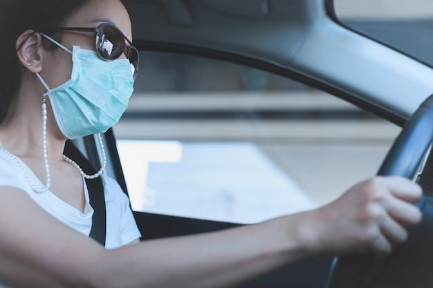 Donna alla guida di un'auto con maschera medica e occhiali da sole sul viso assistenza sanitaria e protezione dai virus