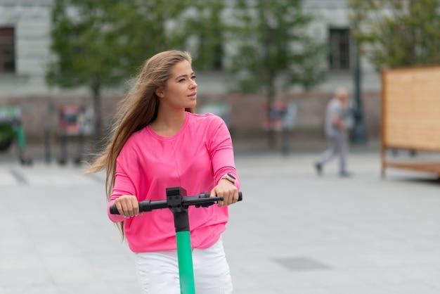Donna che guida uno scooter in una città, mobilità urbana e concetto di trasporto ecologico sostenibile