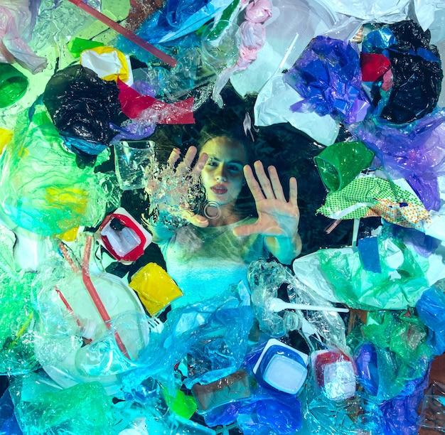 Donna che annega in acqua sotto il mucchio di plastica dei destinatari, immondizia. bottiglie usate e pacchi che riempiono l'oceano mondiale uccidendo persone. ecologia, concetto di ambiente, inquinamento da plastica e vetro, disastro naturale.