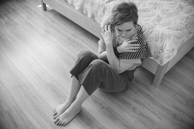 Donna tossicodipendente e alcolismo da solo depressione stress seduto sul pavimento nella sua camera da letto