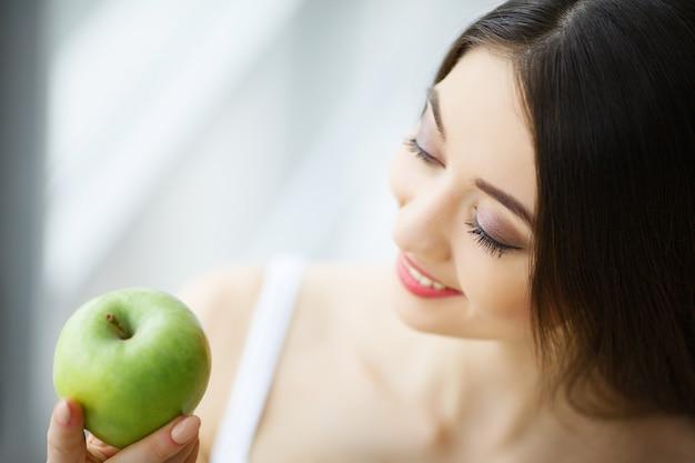 Donna che mangia mela. bella ragazza con i denti bianchi che morde la mela. immagine ad alta risoluzione