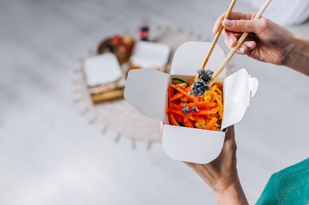 Donna che mangia le tagliatelle cinesi asiatiche dell'alimento con le verdure nella scatola del wok facendo uso delle bacchette. consegna del cibo. pranzo da asporto.