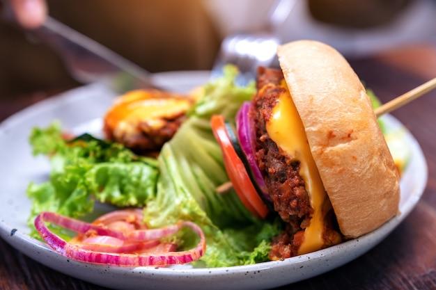 Donna che mangia hamburger di manzo con coltello e forchetta nel ristorante