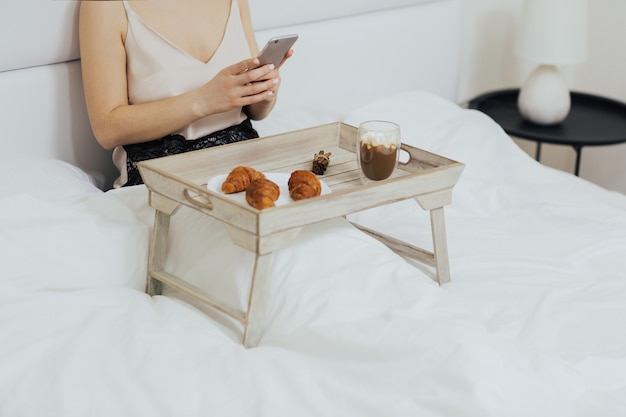 Donna che mangia colazione da un vassoio di legno mentre era seduto a letto