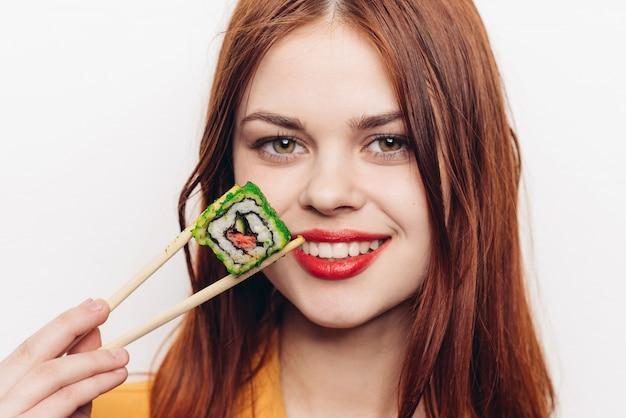 Donna che mangia i rotoli colorati con le bacchette di bambù