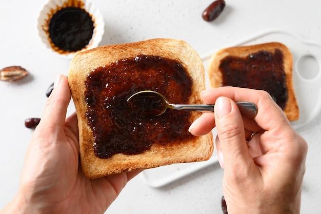 Donna che mangia pane tostato croccante con marmellata di datteri su bianco