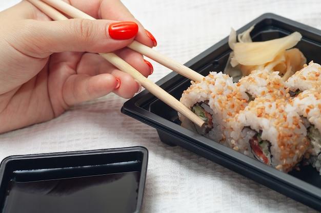 Donna che mangia consegnato a casa sushi da un contenitore con bastoncini giapponesi messa a fuoco selettiva
