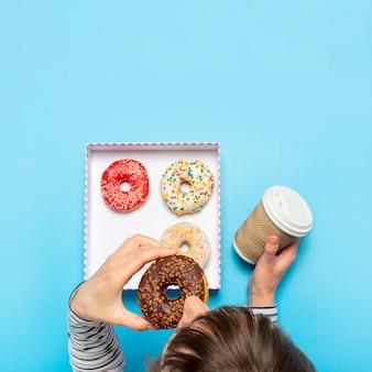 Donna che mangia una ciambella e beve caffè su un blu. negozio di pasticceria di concetto, pasticceria, caffetteria