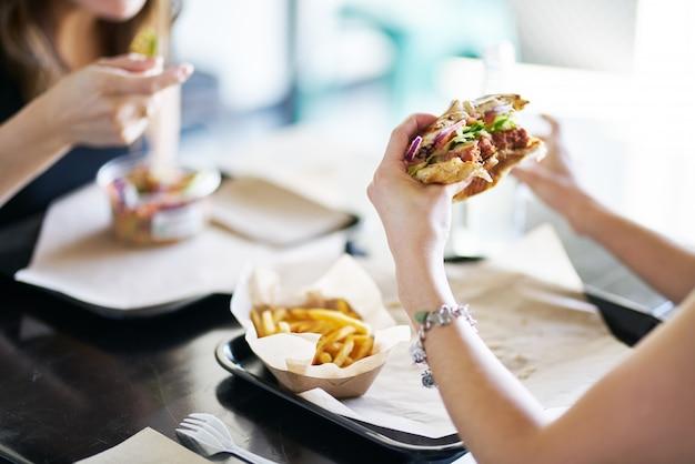 Donna che mangia mangiare hamburger senza carne vegano nel ristorante